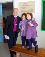 ELCA California Bishop Dean Nelson at Dar al Kalima School with students at the plaque comemmorating donors from his synod