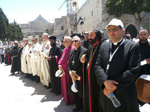 Bishop Younan stands with the Heads of Churches during the Pontifical Mass in Bethlehem