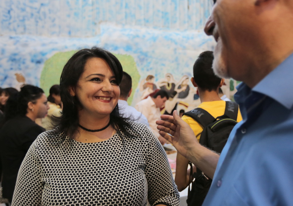 Ms. Rabadi smiles while receiving congratulations